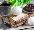 Wine, egg, bitter salad leaves, matzot and haroset - traditional jewish passover celebration elements.